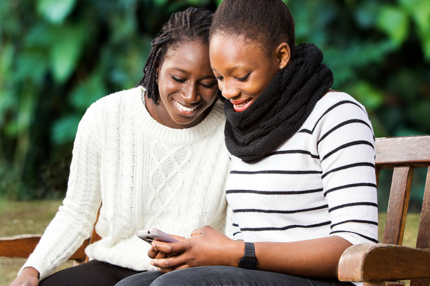 51235376 - close up portrait of two african american teenage girlfriends socializing on smart phone. girls sitting on wooden bench in park against green background.